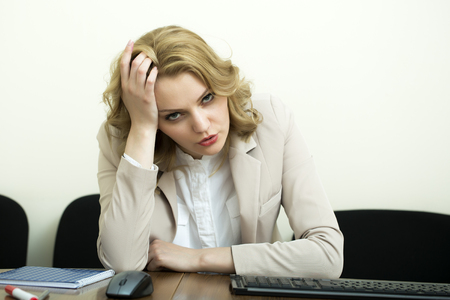 blonde curly hair: Tired beautiful business woman with blonde curly hair in jacket sitting at table underlaying looking forward on white wall background, horizontal picture