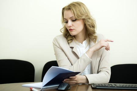 blonde curly hair: Busy attractive business woman with blonde curly hair in jacket sitting at table looking in opened notebook on white wall background, horizontal picture