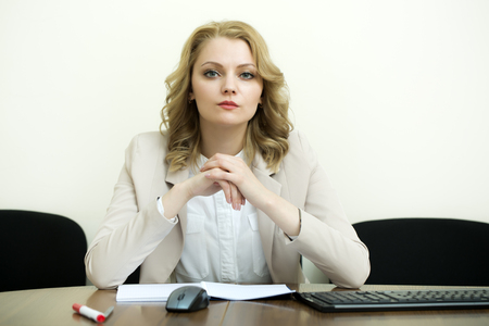 office appliances: Efficient pretty business woman with blonde curly hair in jacket sitting at table with opened notebook looking forward on white wall background, horizontal picture Stock Photo