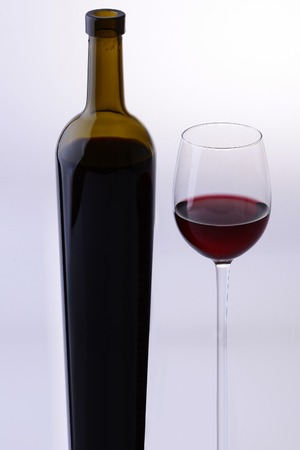 two objects: Two objects oblong of green full bottle and glass goblet with red dessert wine standing together isolated on grey white studio background, vertical picture Stock Photo