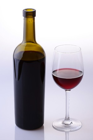 two objects: Two objects of green full bottle and glass bocal with red dessert wine standing near each other isolated on grey white studio background, vertical picture