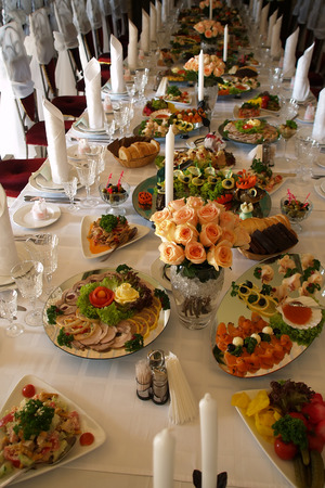 holiday catering: Long spread served festively decorated table with rose bouquets fabric napkins white candles and different snacks with nobody, vertical picture