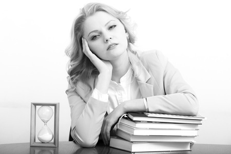 black secretary: Portrait of tired attractive secretary woman with curly hair in jacket sitting at table with heap of books and sand hour glass clock on light wall background black and white, horizontal picture Stock Photo