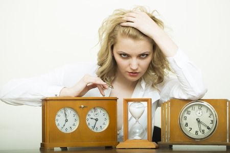 hour glass figure: Attractive serious waiting young blonde business woman sitting in shirt with wooden sand glass and clock with dial looking forward on white background, horizontal picture