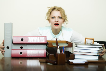 office appliances: Beautiful young blonde business woman sitting in office at table with many documents files folders has a lot of work holding all items in heap on white background, horizontal picture
