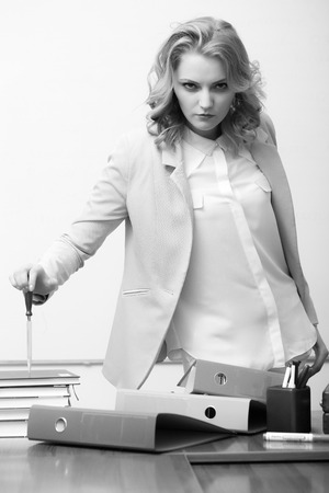 office appliances: Pretty serious business woman in jacket standing near table with many folders holding knife for cutting paper looking forward black and white, vertical picture