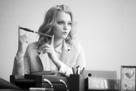 sexy secretary: Pretty cool mujer de negocios atractiva que se sienta a la mesa con muchos aparatos de oficina sosteniendo el cuchillo para cortar papel mirando lejos copyspace blanco y negro, imagen horizontal Foto de archivo