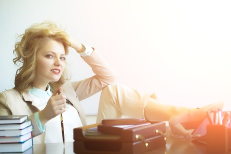 office appliances: Cute smiling sexy business woman sitting at table with many office appliances holding knife for cutting paper looking forward on white background with highlight copyspace, horizontal picture