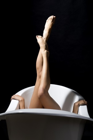 feet naked: Three positions of black background white bathtab and sexy slender beautiful female legs with soft skin sticking out of bath and hands holding side, vertical picture Stock Photo