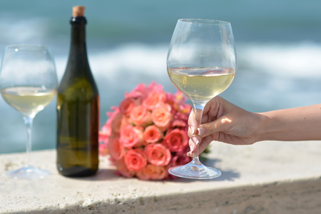 cut flowers: Closeup of female hand green bottle one wedding coral rose bouquet and two glasses with white wine standing on parapet sunny day outdoor on wavy blue ocean or sea water background, horizontal picture Stock Photo