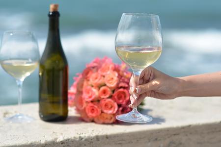 vaso de agua: Primer de la mano femenina verde botella de un coral de la boda Ramo color de rosa y dos vasos de vino blanco de pie en el parapeto d�a soleado al aire libre en el oc�ano azul ondulado o fondo de agua de mar, cuadro horizontal Foto de archivo
