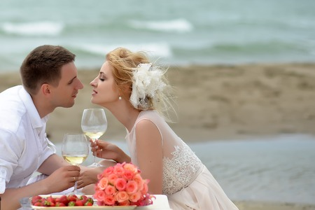 proposing a toast: Beautiful tender wedding couple of young man and woman sitting on ocean beach shore at table with rose bouquet red strawberry kissing and drinking white wine from glasses copyspace, horizontal picture Stock Photo