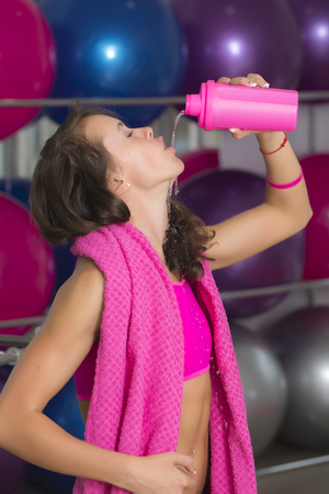 thirsting: Beutiful sexy young brunette sports woman standing in sport hall with towel on shoulders thirsting and drinking water from plastic pink bottle, vertical picture