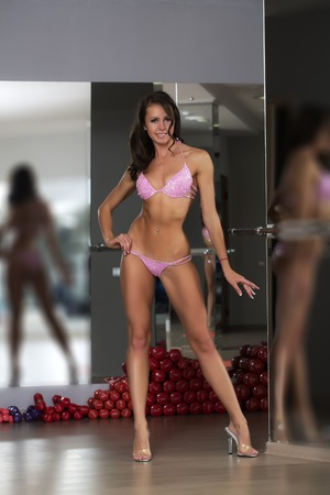 sexy boobs: Beautiful sexual sporty fitness brunette woman with muscular sexy body standing on high heels in pink glamour bikini with soarkles near heap of red dumbells in sport hall, vertical picture