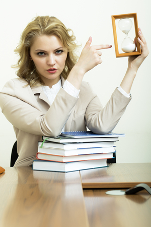 office appliances: Portrait of serious pretty business woman with blonde curly hair in jacket showing on sand hour glass clock sitting at table with heap of books on white wall background, vertical picture Stock Photo