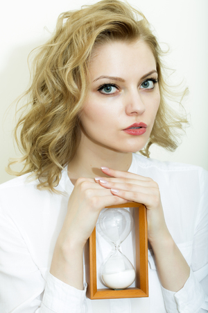 hour glass figure: Portrait of pretty thoughtful secretary woman sitting in shirt holding wooden sand glass looking forward on white background, vertical picturepicture Stock Photo