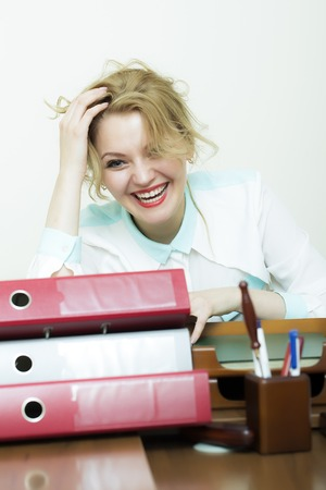 pen and paper: Beautiful laughing young blonde business woman sitting in office at table with many documents files folders has a lot of work on white background, vertical picture