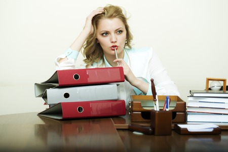 office appliances: Pretty thoughtful working business woman sitting in office at table with many documents books files folders has a lot of work holding pen on white background, horizontal picture