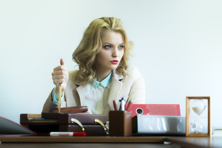 office appliances: Beautiful serious sexy business woman sitting at table with many office appliances holding knife for cutting paper looking away on white background, horizontal picture