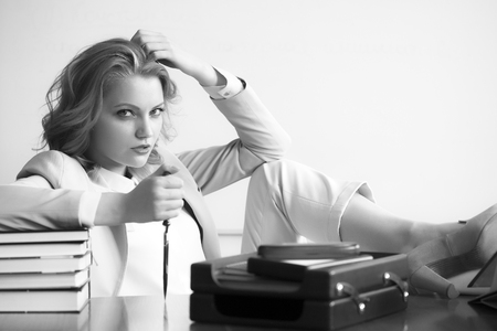 office appliances: Attractive sexual business woman sitting at table with many office appliances holding knife for cutting paper looking forward black and white copyspace, horizontal picture