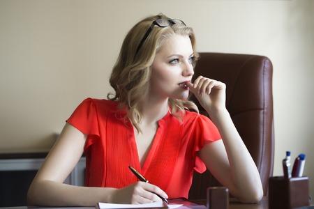若く魅力的なエレガントなスマート ブラウンのオフィスに座っている金髪の働くビジネス女性赤いブラウスとメガネの考え方、書き方よそ見革椅子