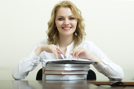 office appliances: Portrait of smiling beautiful young student girl with blond curly hair in blouse sitting at table with heap of books and reading on white wall background, horizontal picture Stock Photo