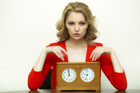 hour glass figure: Beautiful sexy waiting young blonde secretary woman sitting in red blouse with old wooden clock looking forward on white background, horizontal picture Stock Photo