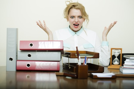 office appliances: Pretty young crazy secretary girl with curly hair has stress sitting at table with many folders documents and office appliances shouting on white background, horizontal picture Stock Photo