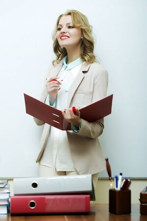 office appliances: Beautiful smiling young blond business woman in jacket holding red paper case writing with marker standing on white background, vertical picture