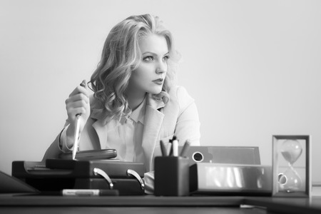 office appliances: Beautiful pensive sexy business woman sitting at table with many office appliances holding knife for cutting paper looking away black and white, horizontal picture