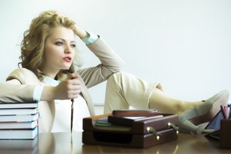 office appliances: Pretty thoughtful sensual business woman sitting at table with many office appliances holding knife for cutting paper looking forward on white background copyspace, horizontal picture