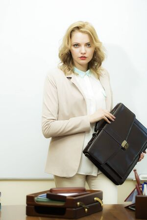 office appliances: Serious pretty young business woman with blonde curly hair holding one black leather briefcase standing near office table looking forward on white background, vertical picture