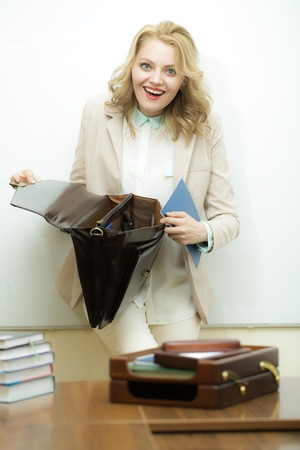 office appliances: Laughing attractive young business woman with blonde curly hair holding one open black leather briefcase putting documents inside standing near office table on white background, vertical picture