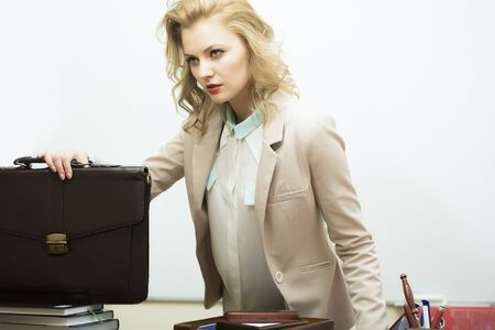 female boss: Serious concentrated beautiful young business woman with blonde curly hair near black leather briefcase looking away standing on white background copyspace, horizontal picture Stock Photo