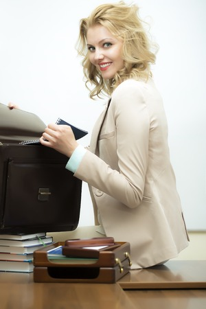 office appliances: Sexy smiling cute young business woman with blonde curly hair opening black leather briefcase looking forward standing on white background, vertical picture