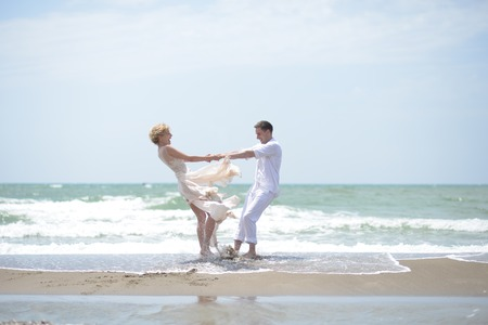 windy day: Beautiful happy young wedding Pair of boy and girl in white spinning on ocean beach coast on windy weather sunny day outdoor on blue sky background, horizontal picture