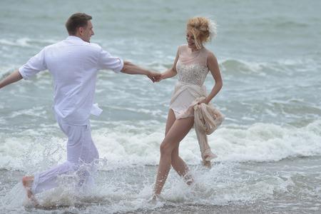 parejas romanticas: Hermosa feliz pareja encantadora boda de paople j�venes tomados de la mano de pie en el agua en la playa del oc�ano costa y sonriente, imagen horizontal
