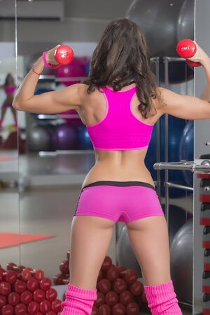 scrawny: Back view of sexy fitness young woman with beefy bottom in pink uniform holding red dumbells standing with feet apart in sport hall training indoor, vertical picture