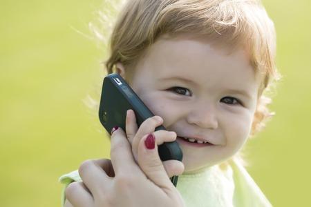 ojos hermosos: Retrato del pequeño bebé hermoso sonriente con el pelo rubio rizado y explotación linda cara y hablando en el teléfono móvil negro día soleado al aire libre en el fondo de hierba verde, cuadro horizontal