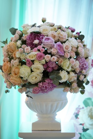 flower arrangement: Decorative wedding bouquet of fresh beautiful flowers of roses and peony white pink violet purple yellow lilac and orange colours in big vase on blue curtain background, vertical picture