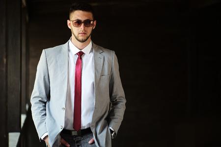 poses de modelos: Apuesto hombre de negocios serio sin afeitar y sexual en lazo rojo sol vidrios de la camisa blanca chaqueta gris que se coloca al aire libre con las manos en los bolsillos sobre fondo negro copyspace, cuadro horizontal