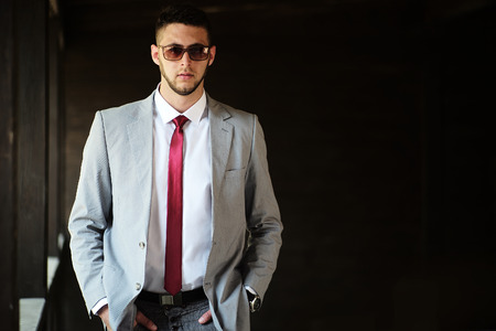 Handsome sexual serious unshaven businessman in grey jacket white shirt red tie and sun glasses standing outdoor with hands in pockets on black background copyspace, horizontal picture 免版税图像