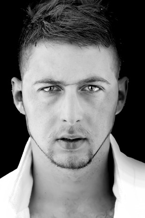 Portrait of sexy young handsome serious boy with unshaven face with scar and stylish hairdo looking forward standing in shirt with open collar black and white, vertical picture