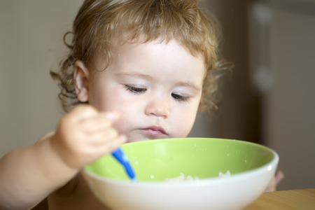 baby with spoon: Portrait of serious small male kid with blonde curly hair and round cheecks eating from green plate with spoon closeup, horizontal picture
