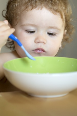blonde curly hair: Portrait of interesting little male kid with blonde curly hair and round cheecks eating from green plate with spoon closeup, vertical picture Stock Photo