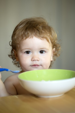 blonde curly hair: Portrait of cute sweet little boy with blonde curly hair and round cheecks eating from green plate with spoon closeup, vertical picture