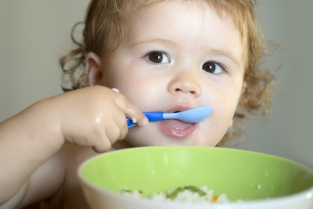 blonde curly hair: Portrait of cute little male child with blonde curly hair and round cheecks eating from green plate with spoon closeup, horizontal picture Stock Photo