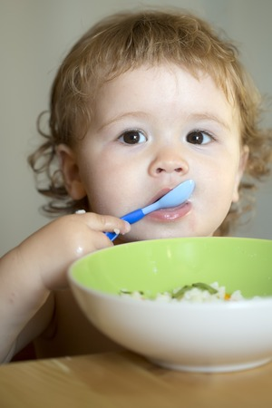 blonde curly hair: Portrait of cute little male kid with blonde curly hair and round cheecks eating from green plate with spoon closeup, vertical picture Stock Photo