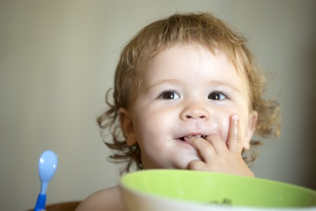 blonde curly hair: Portrait of sweet small smiling baby boy with blonde curly hair and round cheecks eating from green plate holding spoon and lick fingers closeup, horizontal picture Stock Photo