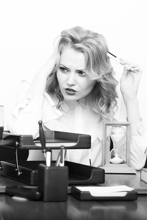 office appliances: Cute young tired secretary girl with curly hair has headache sitting at table with many folders documents and office appliances black and white, vertical picture